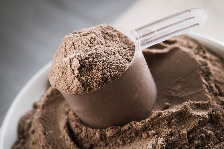 A scoop of chocolate flavored protein powder